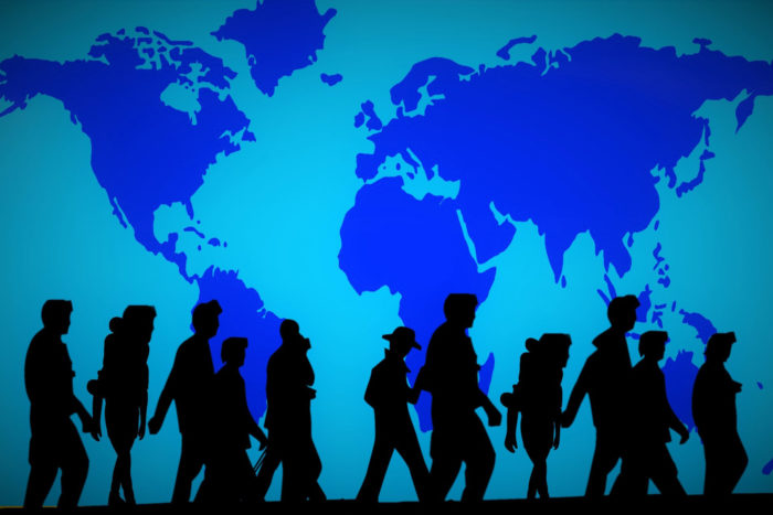 Silhouettes of people/refugees walking against a blue tinted backdrop with an outline of the world printed on it.